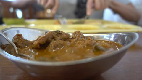 blur man enjoys eating and dipping on varieties spicy curry Indian foods on table at restaurant