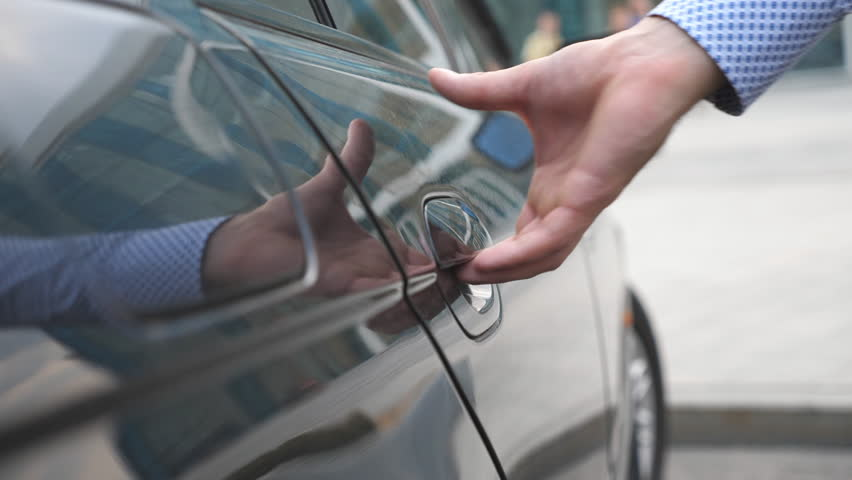 Hand of male businessman opens and holds the car door for the beautiful young woman. Man opening door of automobile for female passenger. Girl get into the auto. Close up Slow Motion | Shutterstock HD Video #31267699