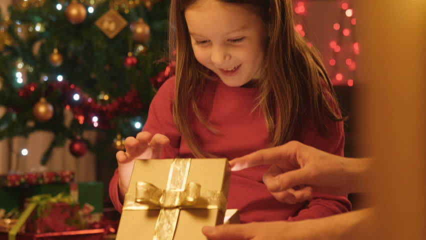 Close-up shot of a cute little girl opening her Christmas present with her mother.  | Shutterstock HD Video #31274299