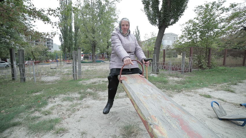 An elderly woman is riding a child's swing.   Shutterstock HD Video #31298497