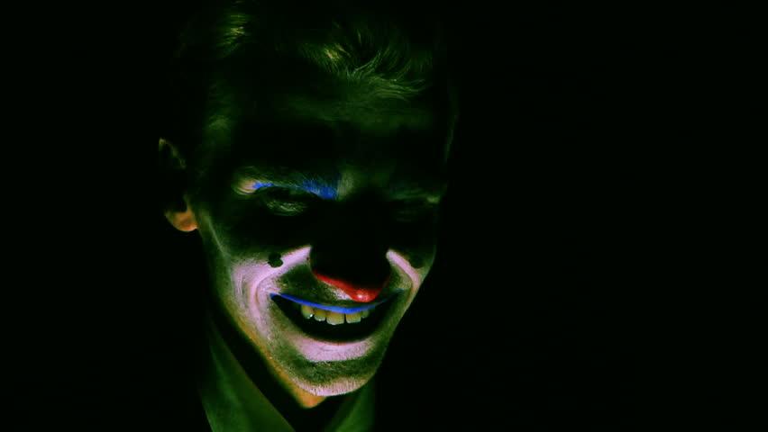 Evil clown man laughs.