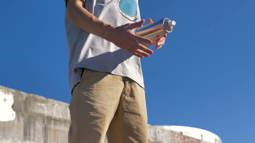 A graffiti artist near a painted wall catches a paint can.