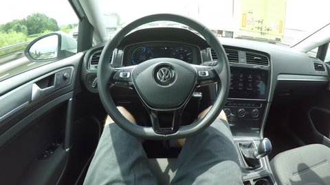 LJUBLJANA, SLOVENIA - MAY 1st 2017: Man in self-steering autonomous VW electric car driving with no hands on multiple lane highway. Driver in innovative self driving Volkswagen autopilot automobile
