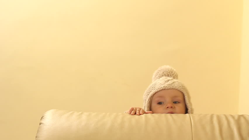 Cute baby head with big fez showing up behind the couch while standing up and practicing first steps