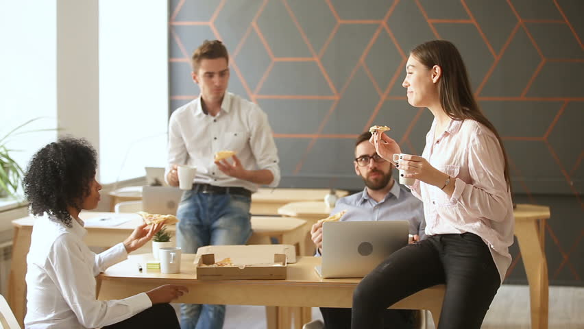 Business team of young people enjoying eating pizza together, millennials group talking having fun sharing lunch in cozy office, good relationships at work, food delivery service and catering | Shutterstock HD Video #31351990