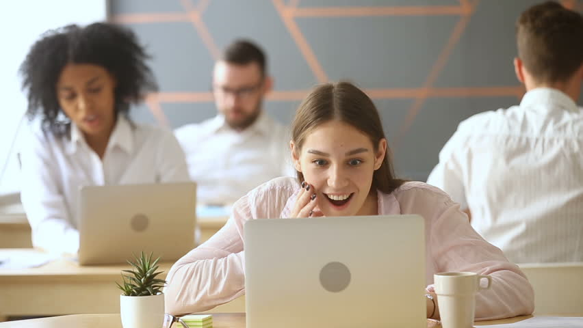 Young excited employee looking at laptop screen with surprise, gossip girl sharing good funny news with coworkers, spreading rumors in coworking office, colleagues talking at workplace, word of mouth | Shutterstock HD Video #31351999