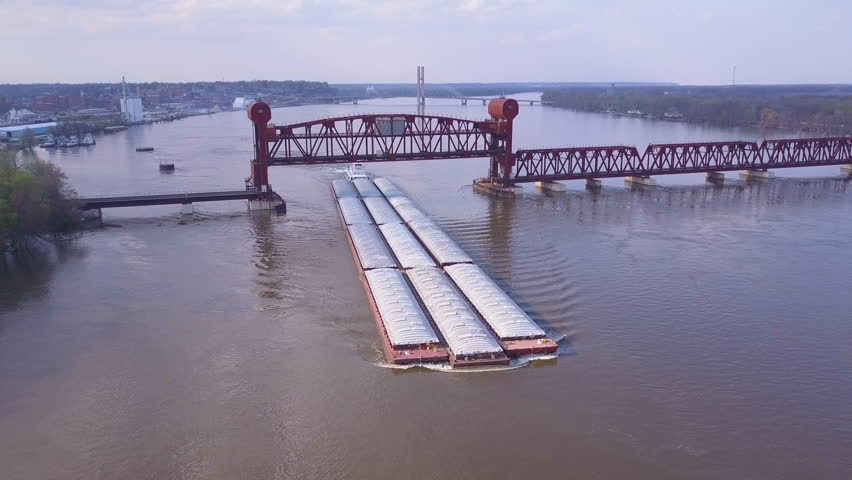 CIRCA 2010s - Mississippi River - A beautiful aerial of a barge traveling under a stel drawbridge on the Mississippi River.