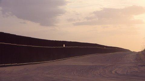 CIRCA 2010s - U.S.-Mexico border - Dust blows at sunset at the border wall at the US Mexico border near Imperial sand dunes, California.