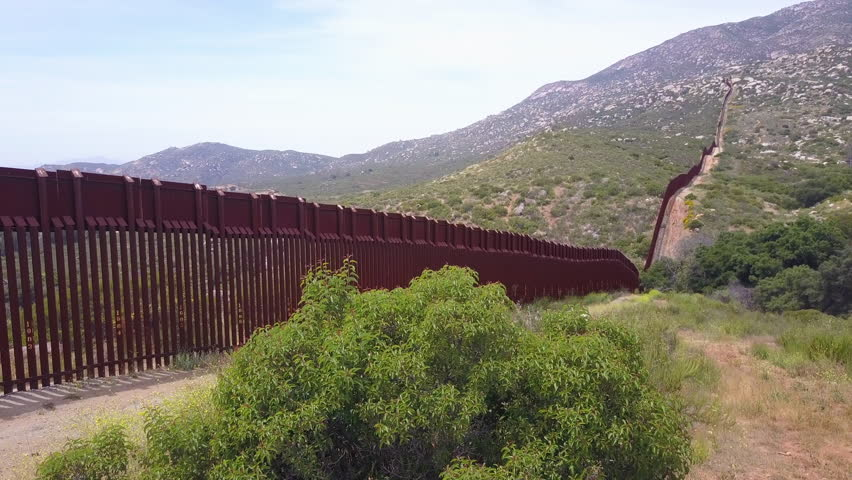 CIRCA 2010s - U.S.-Mexico border - Slow rising aerial along the U.S Mexican border wall fence in a rural area. | Shutterstock HD Video #31373929