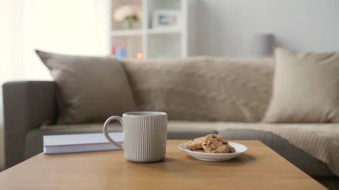 cozy home concept - chocolate oatmeal cookies and mug with hot drink on wooden table in living room