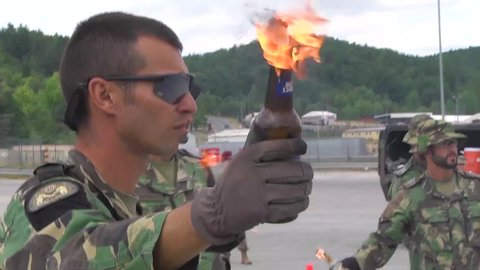 CIRCA 2010s - Riot police practice combat exercises against molotov cocktail throwing protesters.