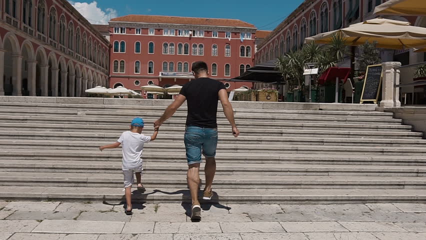 The father and his son have fun climbing up the stairs on Split's square. Croatia slow motion