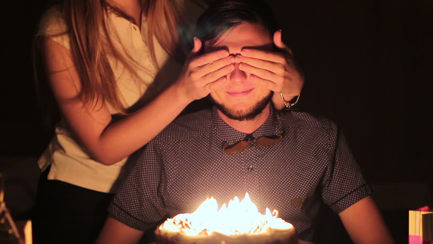 Young couple celebrating a birthday. Young guy blows out the candles on his birthday cake
