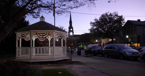 A nitghttime view of a small town street, gazebo, and traffic activity. Pittsburgh suburbs.