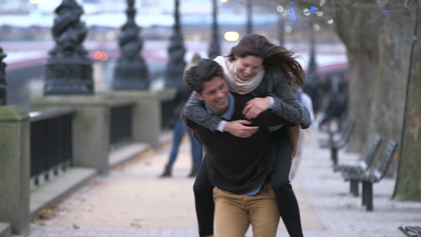 Piggyback. Casually dressed heterosexual couple having fun together in a big city. They are running and laughing.