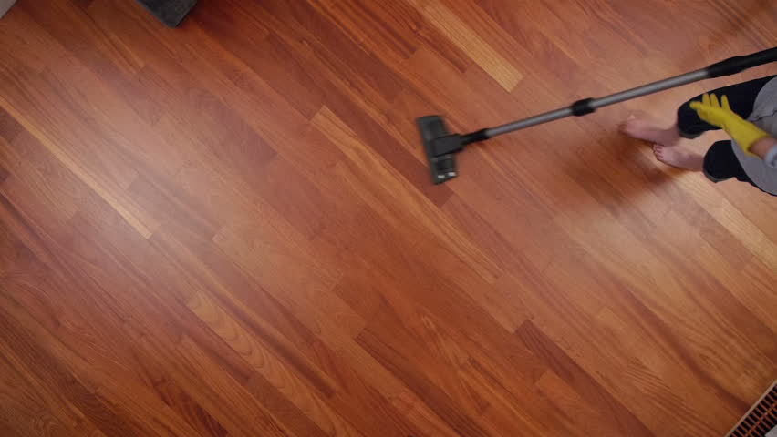overhead shoot of cleaning lady with a vacuum cleaner