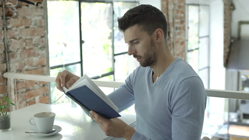 Handsome man in blue sweater sitting in the cafe and reading stupid book, steadycam shot  | Shutterstock HD Video #31431289
