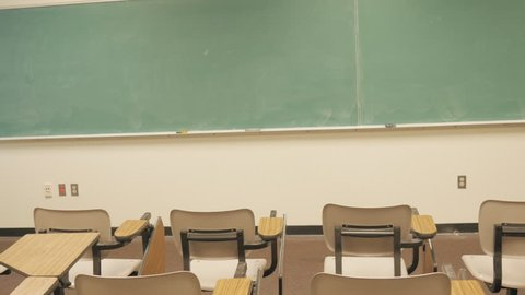 Handheld shot of a blackboard and school desks in an empty classroom. The barren lecture hall has been evacuated due to budget cuts, low attendance and student loans.