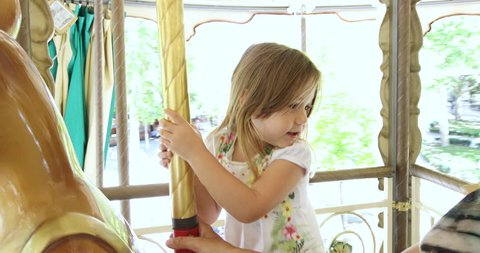 4k video. Four years old blonde pretty girl riding and enjoying on an animal in a carousel, next to mother