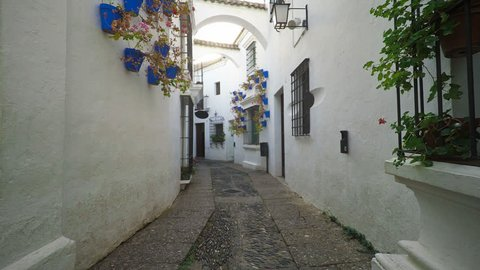 Smooth camera steady slide shot around old south Spain village narrow street, with white walls, beautiful facades with flowers, perfect for cinema digital composition or movie clips background