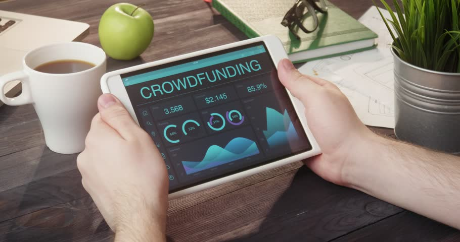 Monitoring crowdfunding data using tablet computer at desk