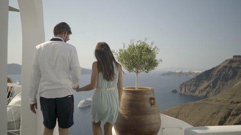 4k travel video following honeymoon couple walking through their hotel outside in santorini