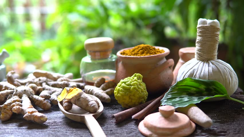 Turmeric powder in clay pot , turmeric capsules and fresh turmeric root on wooden background,footage 4K
