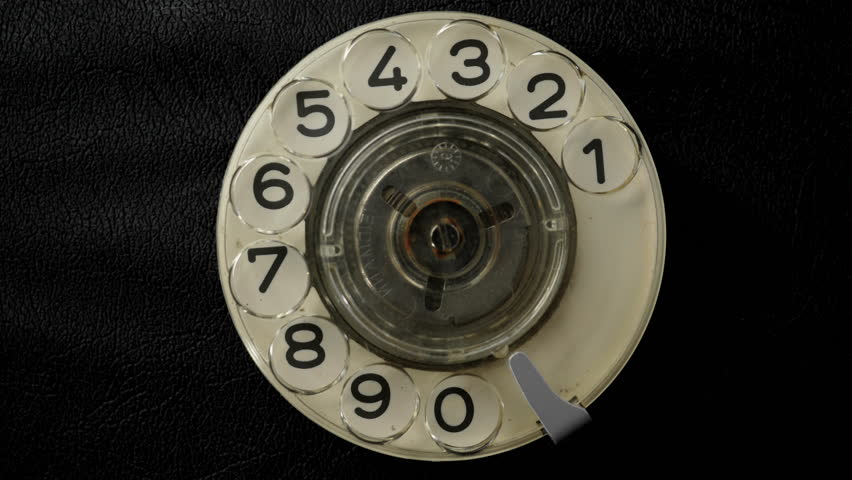 Dialing on an old rotary style telephone. Close-up view.