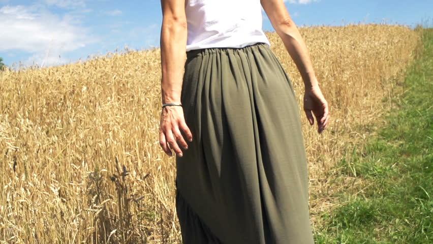 Woman walking into wheat field, super slow motion 240fps