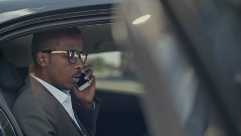 African businessman getting into car on backseat and talking on mobile phone