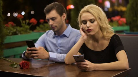 Couple spending time scrolling web pages on phones, impact of modern technology