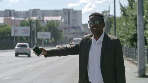 African businessman walking along the side of city street, talking on mobile phone and hailing a taxi cab