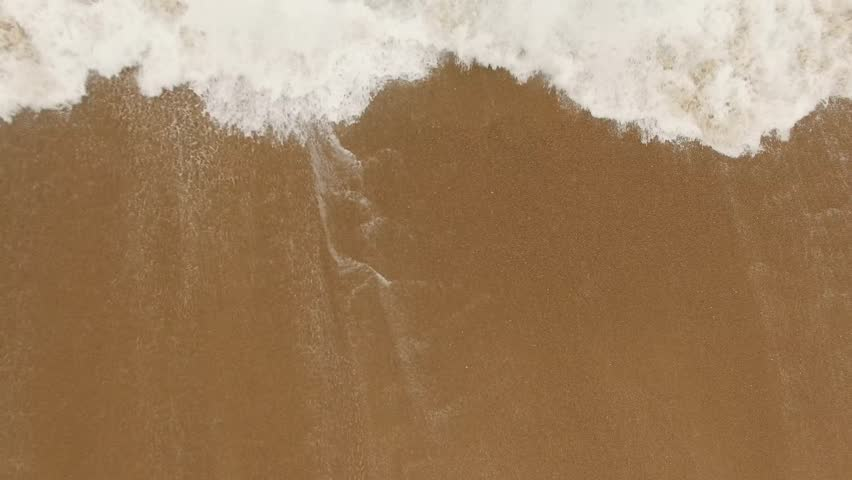 Beautiful ocean waves and splashes on a sandy beach in Nazar , Portugal. Aerial view