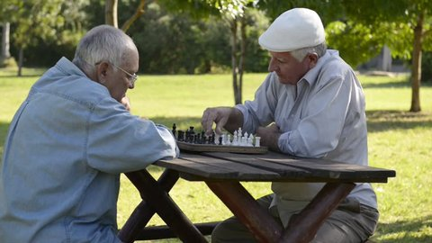 Active retired people, best friends and leisure, group of old men having fun and playing chess game at park. Sequence of wide and medium shot