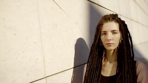 sad girl with long black dreadlocks and ears tunnel is strolling over city streets