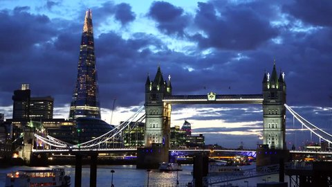London Tower Bridge and the Shard at sunset, blue dark cloudy sky, lightning buildings, ship passing, magical town