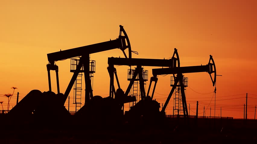 Many crude petroleum naphta drilling extraction pumps under the sunset red sky on oil field industrial platform