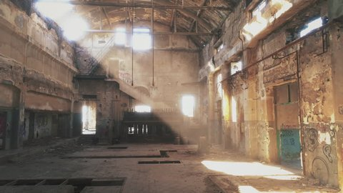 Interior of an abandoned derelict industrial structure. Real time motion shot of a long abandoned and partly demolished industrial factory in Greece.Sun light creeping through holes in the wall.