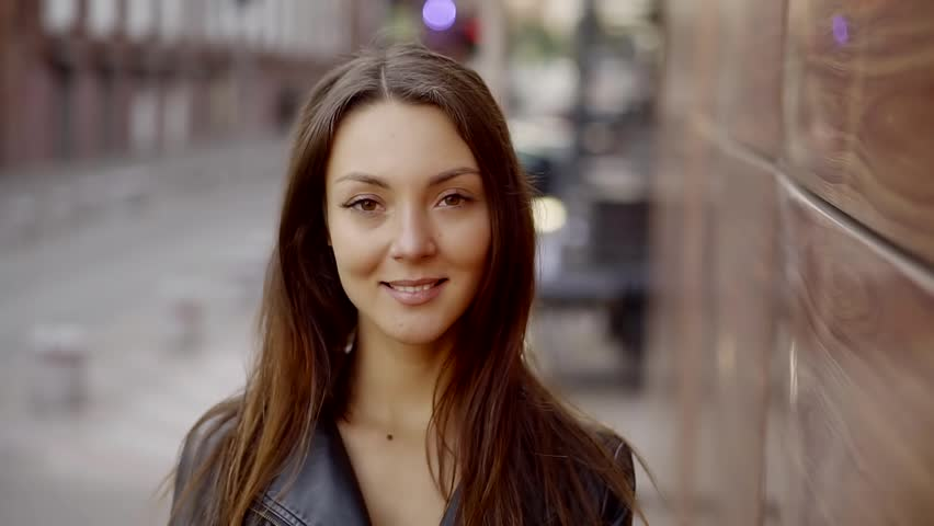 Young sensual woman is standing on a city street in daytime, looking at a camera | Shutterstock HD Video #31649518