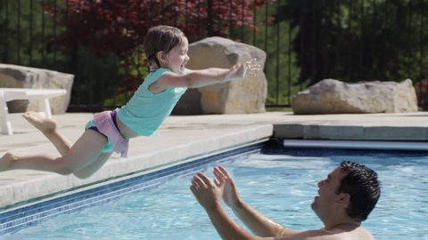 Young girl jumps to father in pool