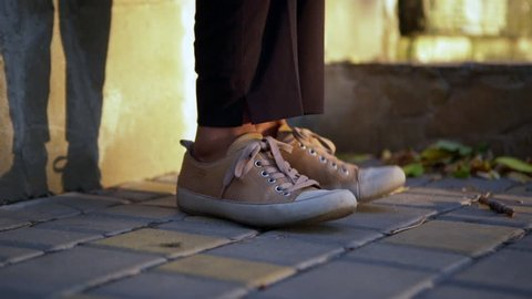closeup picture of woman in sneakers standing on paving stone tapping feet with shadow of legs on wall background during sunny day cropped