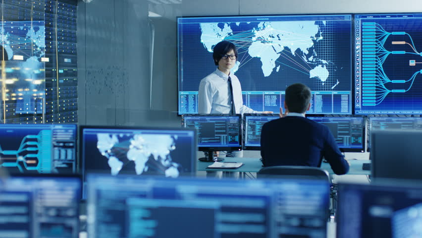 In the System Control Room Manager Holds a Briefing for His Staff Members. They're Work in Data Center and are Surrounded by Multiple Screens Showing Maps, Logistics Data.  | Shutterstock HD Video #31689649