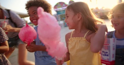 Multi-ethnic best friends children having fun eating cotton candy and pop-corn at summer funfair