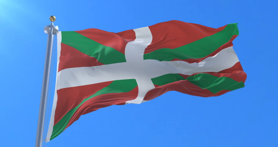Basque country flag named Ikurriña moving slowly by the wind with blue sky, loop