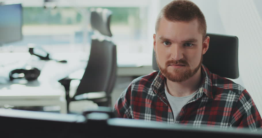 A young bearded man sits at a computer. Works in the office. Feels happy. Contemporary design. | Shutterstock HD Video #31727749