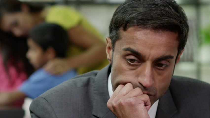 Close up of a man who is stressed about events in his life which are beyond his control. His wife is in the background, looking after their children