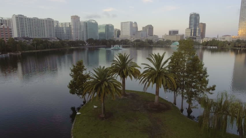 Aerial reveal flying forward & up over Lake Eola fountain in downtown, Orlando, FL.