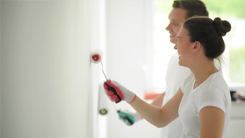 Couple with Platens in Hands Painting the Wall with White Paint in Their Living Room Together. Side View of Woman and Man Doing Apartment Repair.   Shutterstock HD Video #31754953
