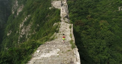aerial flying drone view of young fitness woman trail runner running on top of great wall