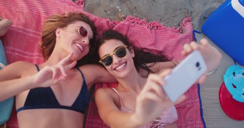 Young hipster women tanning at the beach lying on the sand and taking selfies